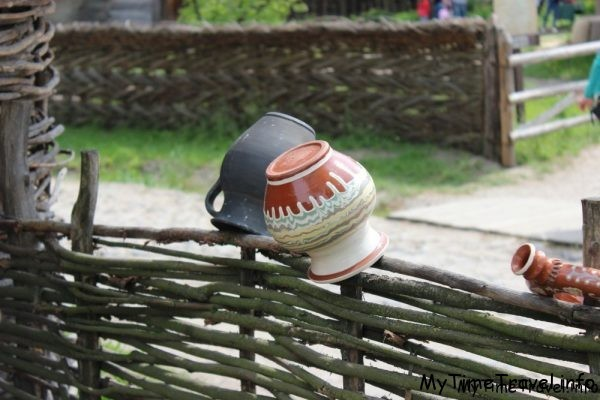 Глиняные горшки на заборе