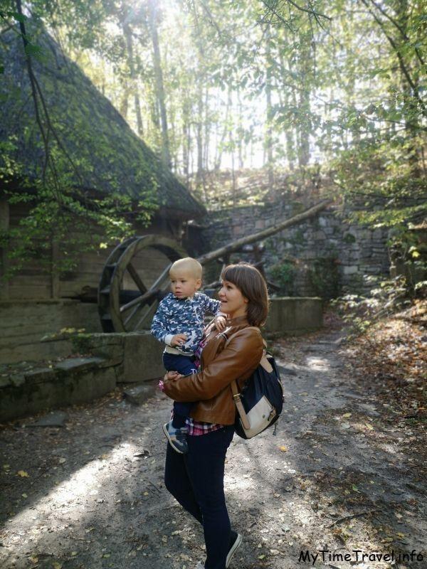 Девушка с ребенком на фоне водяной мельницы