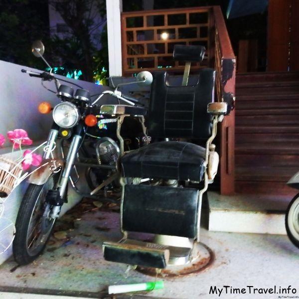 Старое парикмахерское кресло и мотоцикл